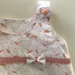 Robe sans manches, motif petites plumes couleur pastelle sur fond blanc. Culotte assortie en double gaz